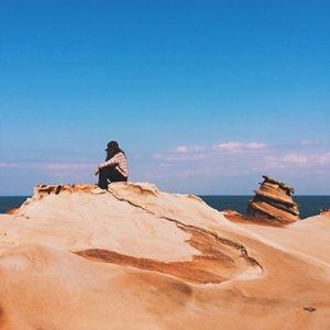 woman relaxing on a rock on taiwan ocean